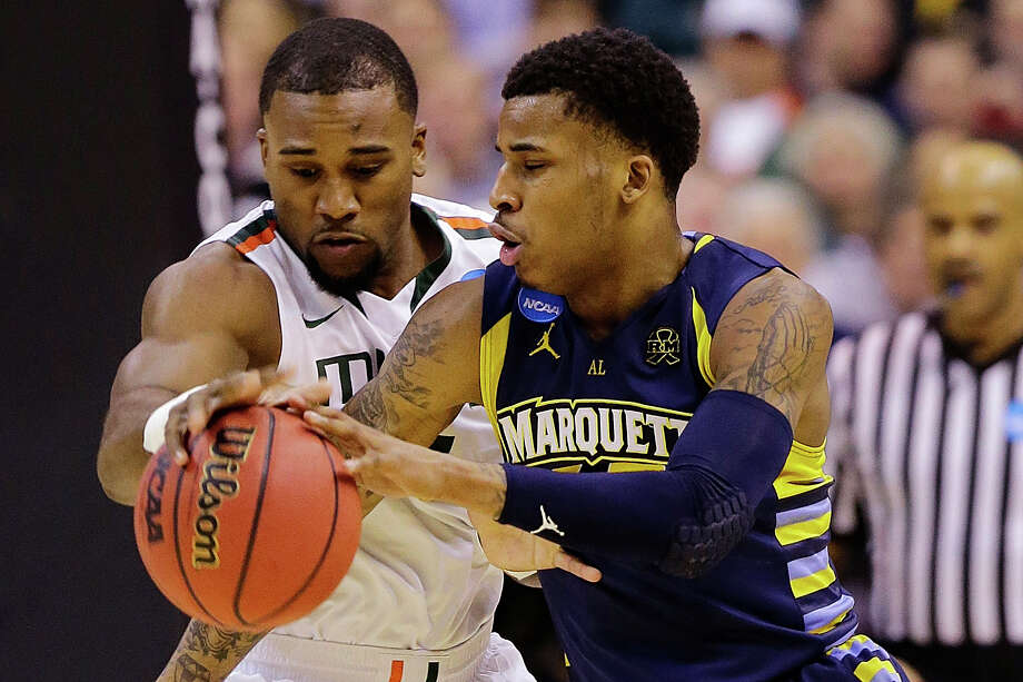 Marquette guard Vander Blue, right, drives around Miami forward Erik Swoope during the first half of an East Regional semifinal in the NCAA college basketball tournament, Thursday, March 28, 2013, in Washington. (AP Photo/Alex Brandon) Photo: Alex Brandon, Associated Press / AP