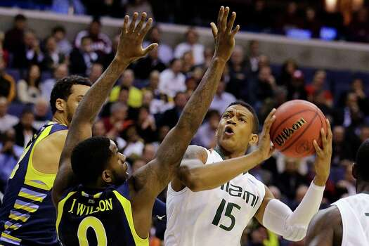 Miami guard Rion Brown (15) shoots over Marquette forward Jamil Wilson (0) during the first half of an East Regional semifinal in the NCAA college basketball tournament, Thursday, March 28, 2013, in Washington. (AP Photo/Alex Brandon) Photo: Alex Brandon, Associated Press / AP