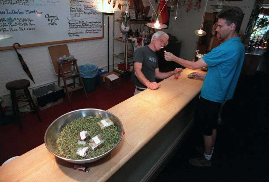 An unidentified Canabis Buyers' Club customer (right) lights up a marijuana cigarette for Dennis Person (behind bar), the establishment's director, on May 2, 1996 in San Francisco. Buyers suffering from AIDS, cancer or conditions with symptoms that marijuana is know to alleviate can purchase the outlawed drug with a doctor's note. In the foreground is a bowl of marijuana and marijuana brownies.Photo By JOHN MABANGLO/AFP/Getty Images