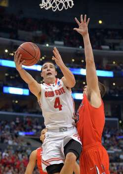 Ohio State's Aaron Craft (4) drives for the basket against Arizona center Kaleb Tarczewski, right, during the second half of a West Regional semifinal in the NCAA men's college basketball tournament, Thursday, March 28, 2013, in Los Angeles. (AP Photo/Mark J. Terrill) Photo: Mark J. Terrill, Associated Press / AP