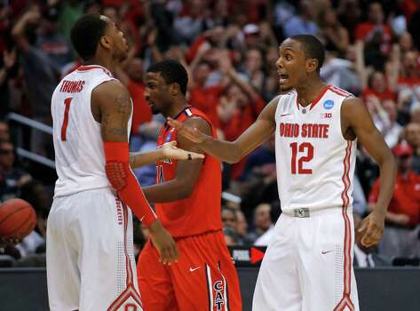 Ohio State's Deshaun Thomas, left, and Sam Thompson celebrate as Arizona's Solomon Hill walks off the court during the second half of a West Regional semifinal in the NCAA men's college basketball tournament, Thursday, March 28, 2013, in Los Angeles. (AP Photo/Jae C. Hong) Photo: Jae C. Hong, Associated Press / AP