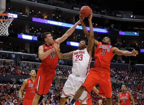 Ohio State's Amir Williams, center, tries to shoot between Arizona defenders Kaleb Tarczewski, left, and Kevin Parrom during the first half of a West Regional semifinal in the NCAA men's college basketball tournament, Thursday, March 28, 2013, in Los Angeles. (AP Photo/Jae C. Hong) Photo: Jae C. Hong, Associated Press / AP