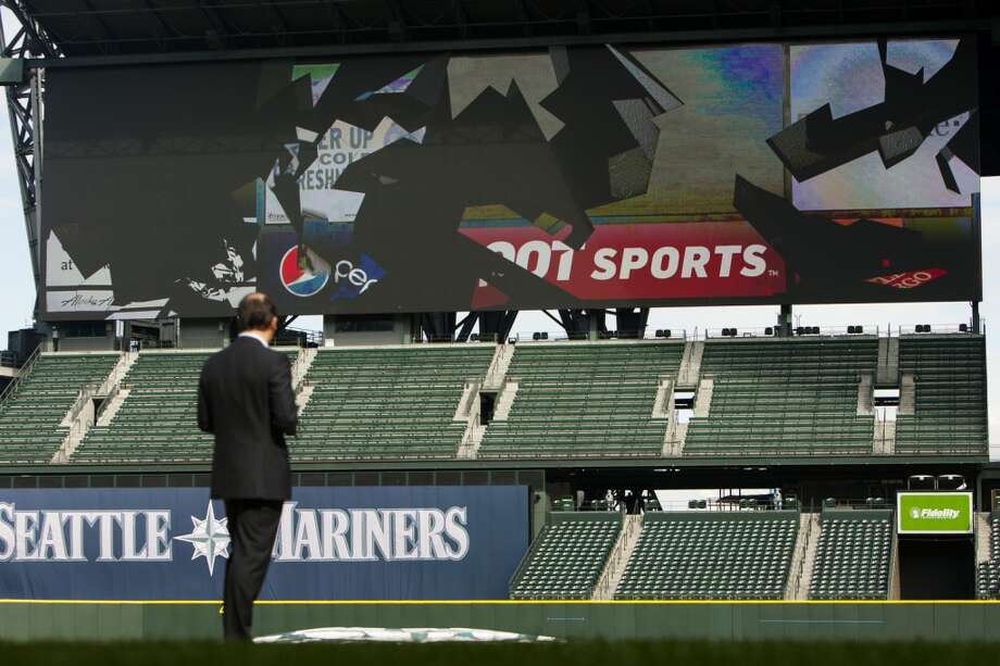 Kevin Martinez, the M's VP of marketing, watches as the old screen view breaks away to reveal Safeco Field's new ''MarinersVision'' high-definition LED display Thursday in Seattle.