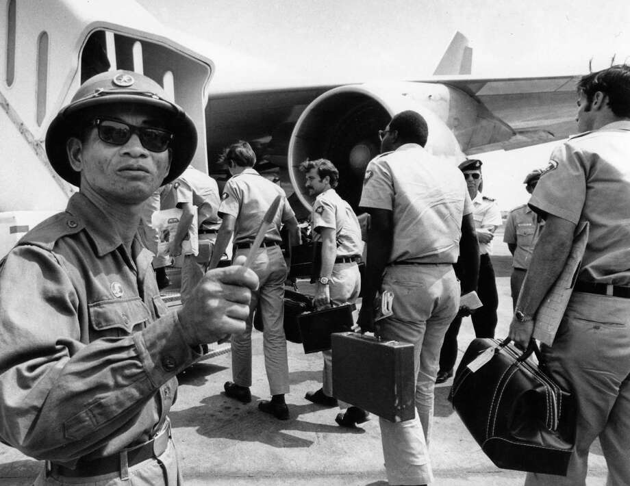 A Viet Cong observer of the Four Party Joint Military Commission counts American troops as they prepare to board jet aircraft at Saigon's Tan Son Nhut airport on March 28, 1973. As the last U.S. combat troops left Vietnam 40 years ago, angry protesters still awaited them at home. Photo: Associated Press File Photo