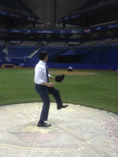 Mayor Julián Castro tries pitching in the Alamodome to Councilman Rey Saldaña.