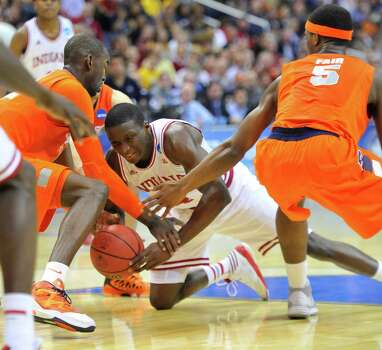 Indiana guard Victor Oladipo (4), center, goes to the floor for the ball between Syracuse center Baye Keita (12) and Syracuse forward C.J. Fair (5) in the first half of an NCAA Tournament East Regional semifinal at the Verizon Center in Washington, D.C., Thursday, March 28, 2013. (Mark Gail/MCT) Photo: Mark Gail, McClatchy-Tribune News Service / MCT