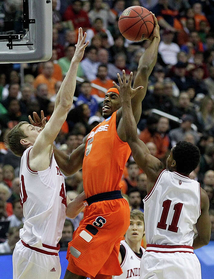 Syracuse forward C.J. Fair (5) heads toward the basket under pressure from Indiana forward Cody Zeller (40) and guard Yogi Ferrell (11) during the first half of an East Regional semifinal in the NCAA college basketball tournament, Thursday, March 28, 2013, in Washington. (AP Photo/Alex Brandon) Photo: Alex Brandon, Associated Press / AP