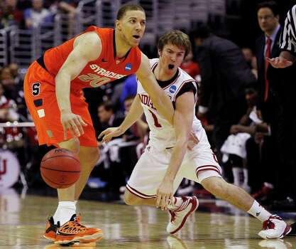 Syracuse guard Brandon Triche (20) keeps the ball away from Indiana guard Jordan Hulls (1) during the first half of an East Regional semifinal in the NCAA college basketball tournament, Thursday, March 28, 2013, in Washington. (AP Photo/Pablo Martinez Monsivais) Photo: Pablo Martinez Monsivais, Associated Press / AP