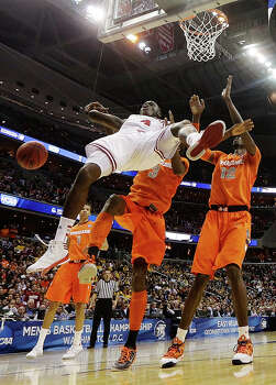 Indiana guard Victor Oladipo (4) falls in front of Syracuse forward Jerami Grant (3) and center Baye Keita (12) during the first half of an East Regional semifinal in the NCAA college basketball game, Thursday, March 28, 2013, in Washington. (AP Photo/Pablo Martinez Monsivais) Photo: Pablo Martinez Monsivais, Associated Press / AP
