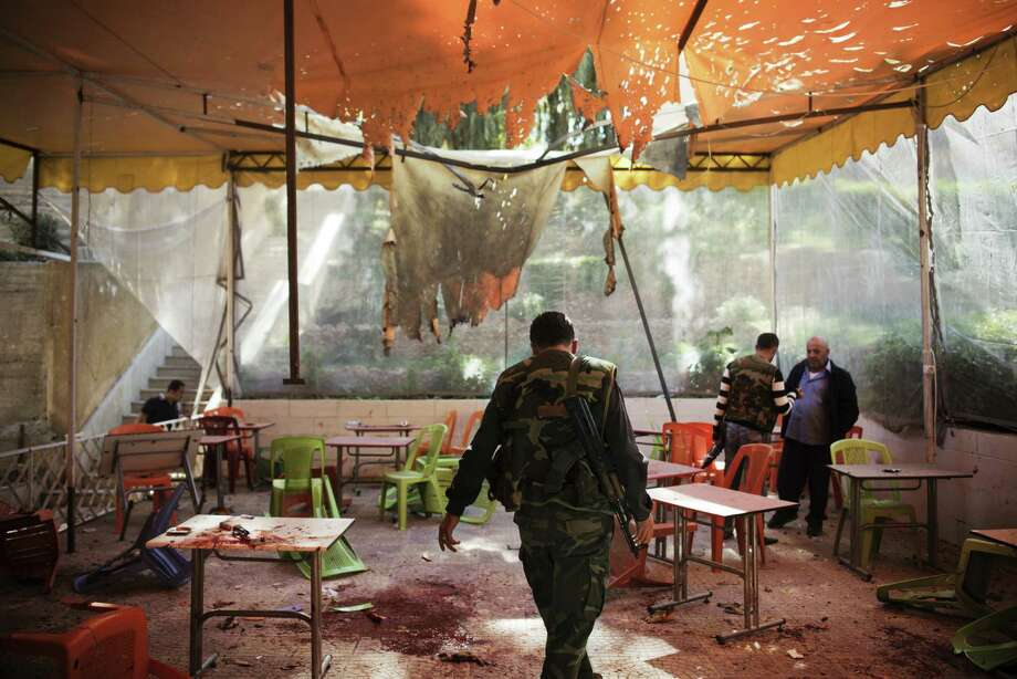 Syrian soldiers and investigators work at an outdoor cafe at Damascus University that was hit by mortar shells. The mortar attack was the deadliest the city has seen amid the civil war. Photo: Andrea Bruce / New York Times