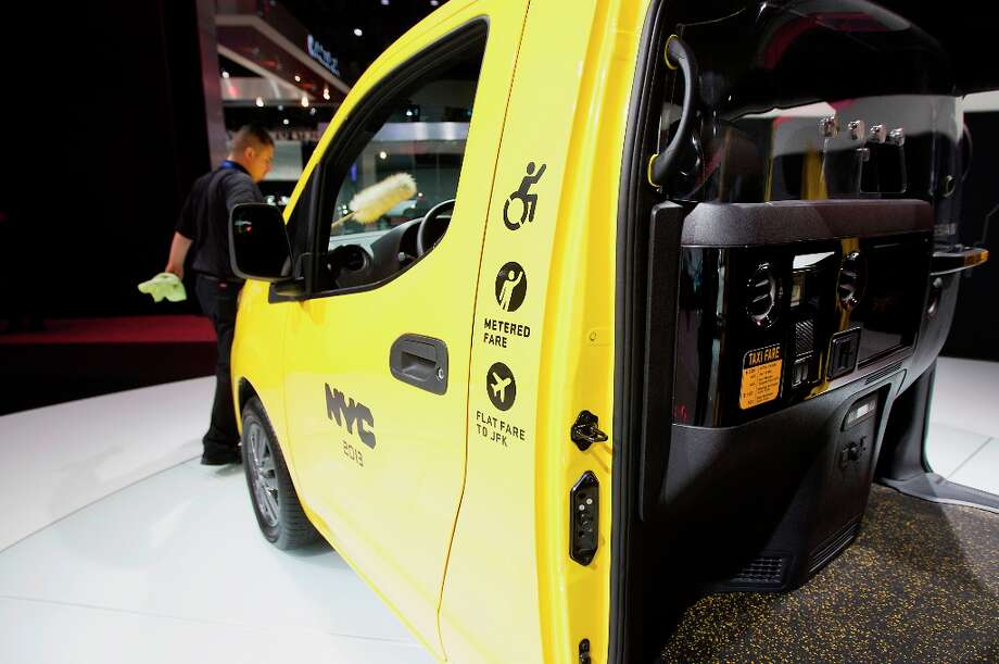 A worker cleans the hood of a Nissan Motor Co. NV200 mobility taxi displayed at the company's booth during the 2013 New York International Auto Show. Photo: Jin Lee, Bloomberg / © 2013 Bloomberg Finance LP