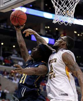 La Salle's Tyrone Garland, left, shoots under heavy pressure from Wichita State's Carl Hall during the first half in NCAA Tournament Sweet 16 action at Staples Center in Los Angeles, California, on Thursday, March 28, 2013. (Yong Kim/Philadelphia Daily News/MCT) Photo: Yong Kim, McClatchy-Tribune News Service / Philadelphia Daily News