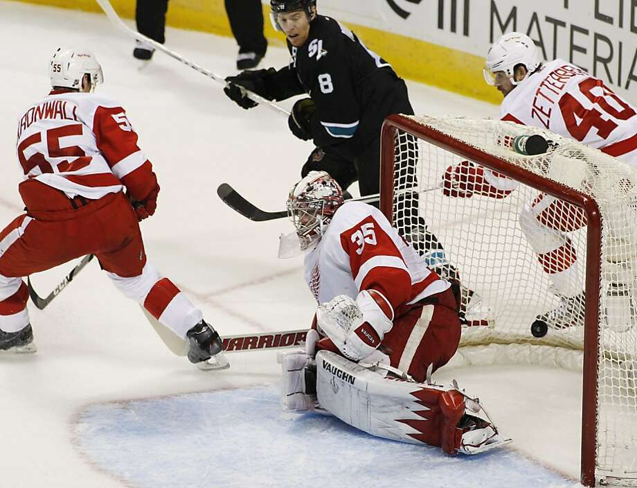 San Jose Sharks' Joe Pavelski (8) scores a goal past Detroit Red Wings goalie Jimmy Howard (35) during the first period of an NHL hockey game, Thursday, March 28, 2013 in San Jose, Calif. Red Wings' Niklas Kronwell (55) is at left and Henrik Zetterberg (40) is at right. (AP Photo/George Nikitin) Photo: George Nikitin, Associated Press