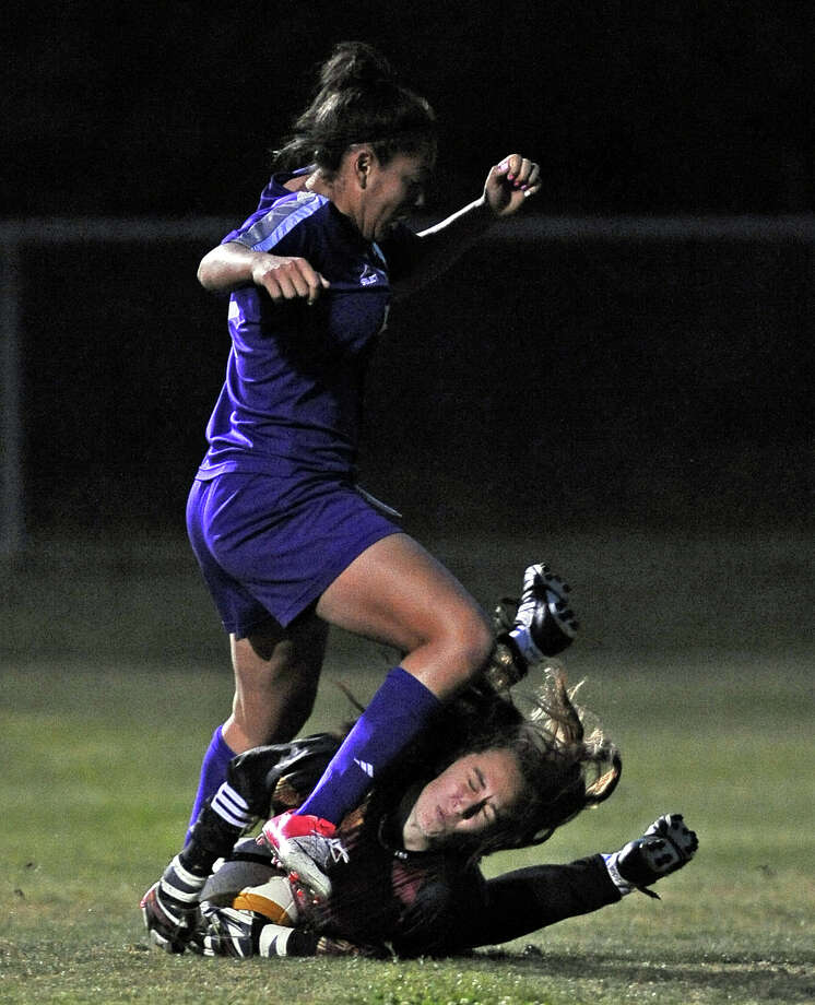 Montgomery goal keeper Schuyler Holder, #15, dives in front of a shot from PN-G freshman Mikayla Johnson, #12, and receives a knee to the face during the Port Neches-Groves High School class 4A area round girls soccer game against Montgomery High School on Thursday, March 28, 2013, in Humble. Photo taken: Randy Edwards/The Enterprise