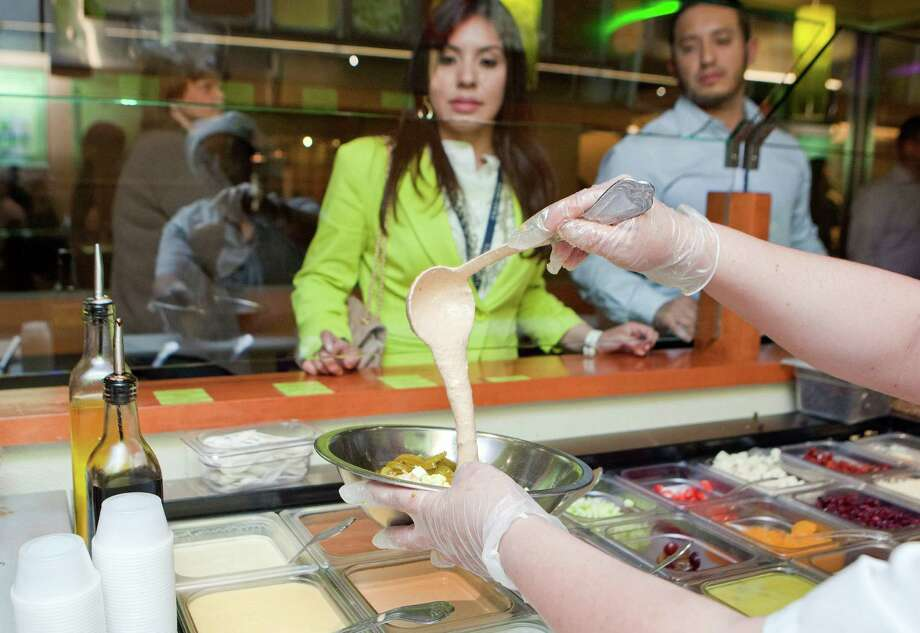 Celeste Salazar waits for her salad. Salata operates from a fairly simple concept: Offer consumers a wide selection of lettuce, chopped veggies, nuts and so on. Photo: Johnny Hanson, Houston Chronicle / © 2013  Houston Chronicle