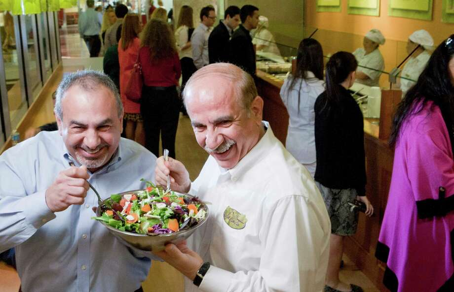 Berge Simonia, left, and Tony Kyoumjian dig in. They're at the first Salata, which opened eight years ago at 919 Milam. Photo: Johnny Hanson, Houston Chronicle / © 2013  Houston Chronicle