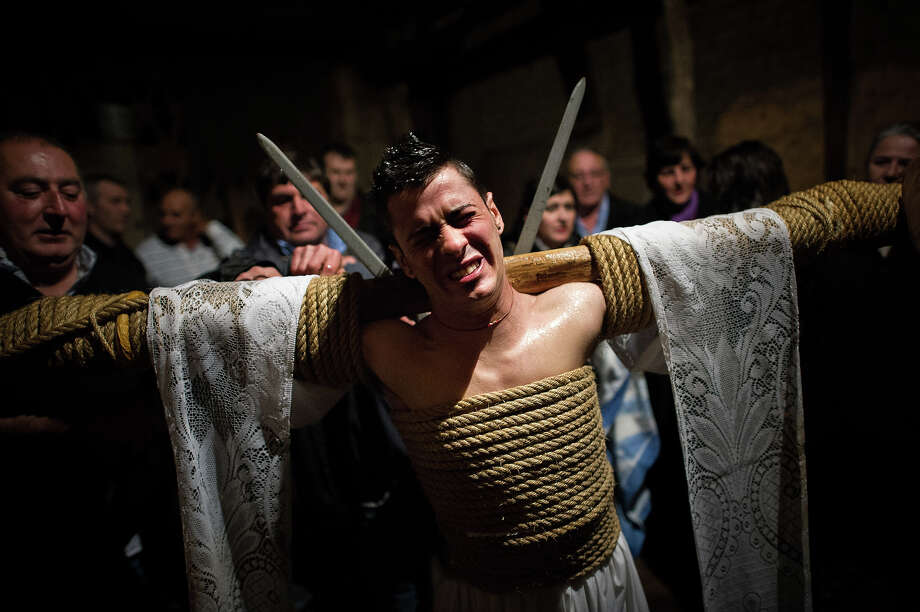 Cesar Higuero Martin, aged 25, reacts after walking the way of the cross or 'Via Crucis' at the end of the procession of the 'Empalaos' on March 29, 2013 in Valverde de la Vera, Spain. Empalaos make the steps of the 'Via Crucis', marking the Stations of the Cross, during the night of Maundy Thursday while bound by rope to a crucifix as an act of penance and to honour a promise made to the Empalaos Brotherhood and the Christ of Vera Cruz, in the town of Valverde de la Vera. The process of dressing the Empalao in the traditional costume is taken with great care, with the family and dressers paying attention to ensure that no harm is caused to the penitent and that they are aided in their recovery, including being massaged and rubbed with rosemary alcohol. Many Spanish towns and villages retain such rites and religious traditions, many passed down from medieval times, across the Easter weekend. Photo: David Ramos, Getty Images / 2013 Getty Images
