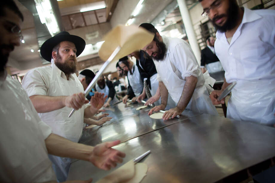 Ultra-Orthodox Jewish men prepare Matzoth, or unleavened bread, in a final preparation before the start at sundown of the Jewish Pesach (Passover) holiday on March 25, 2013 in Bnei Brak, Israel. Religious Jews throughout the world eat matzoth during the eight-day Passover, or Pesach, holiday, The Jewish holiday commemorates the Israelis' exodus from Egypt some 3,500 years ago and their ancestors' plight by refraining from eating leavened food. Passover begins March 25 and ends on the evening of April 02. Photo: Uriel Sinai, Getty Images / 2013 Getty Images