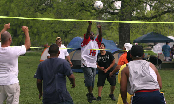 Timothy Woods (center) returns the ball over the net during a friendly game of volleyball on Easter Sunday 2010 at Brackenridge Park. Some people camped out to claim a favorite spot at the park.  Photo: JOHN DAVENPORT, SAN ANTONIO EXPRESS-NEWS / jdavenport@express-news.net