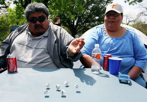 Genard Lugo (left) and Valerie Vara play dice Sunday March 23, 2008 while spending Easter with family in Brackenridge Park. Photo: EDWARD A. ORNELAS, SAN ANTONIO EXPRESS-NEWS / SAN ANTONIO EXPRESS-NEWS