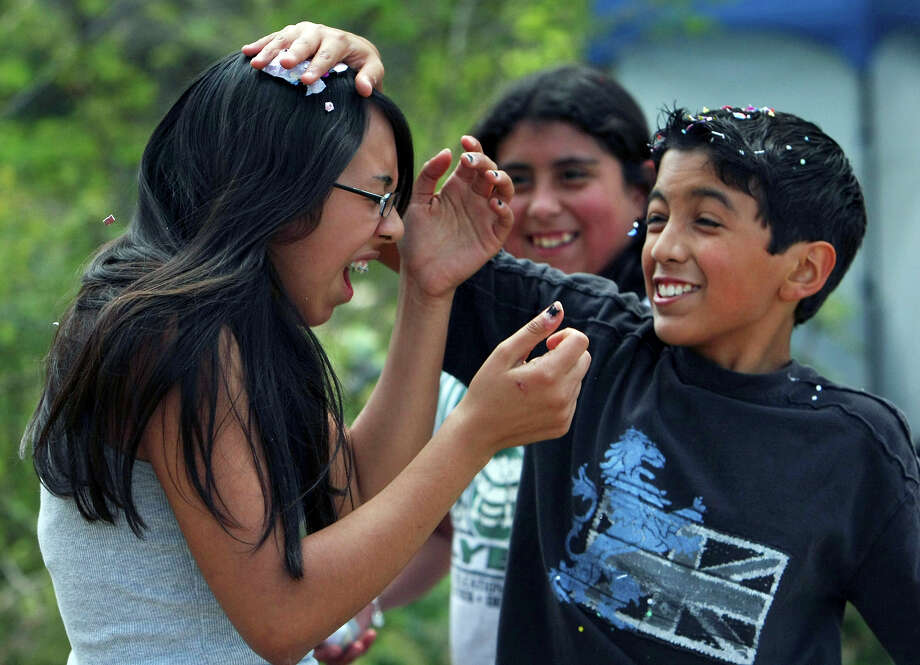 Angela Rodriguez (left) reacts as Keanu Lugo cracks a cascarone on her head Sunday March 23, 2008 while spending Easter with family in Brackenridge Park. Photo: EDWARD A. ORNELAS, SAN ANTONIO EXPRESS-NEWS / SAN ANTONIO EXPRESS-NEWS