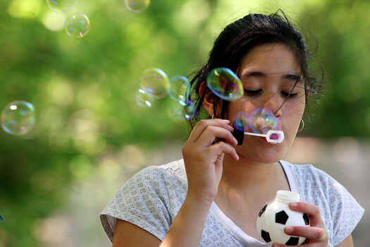 Kristie Hernandez, 12, blows bubbles while spending Easter with her family Sunday April 12, 2009 at Brackenridge Park. Photo: EDWARD A. ORNELAS, SAN ANTONIO EXPRESS-NEWS / eaornelas@express-news.net