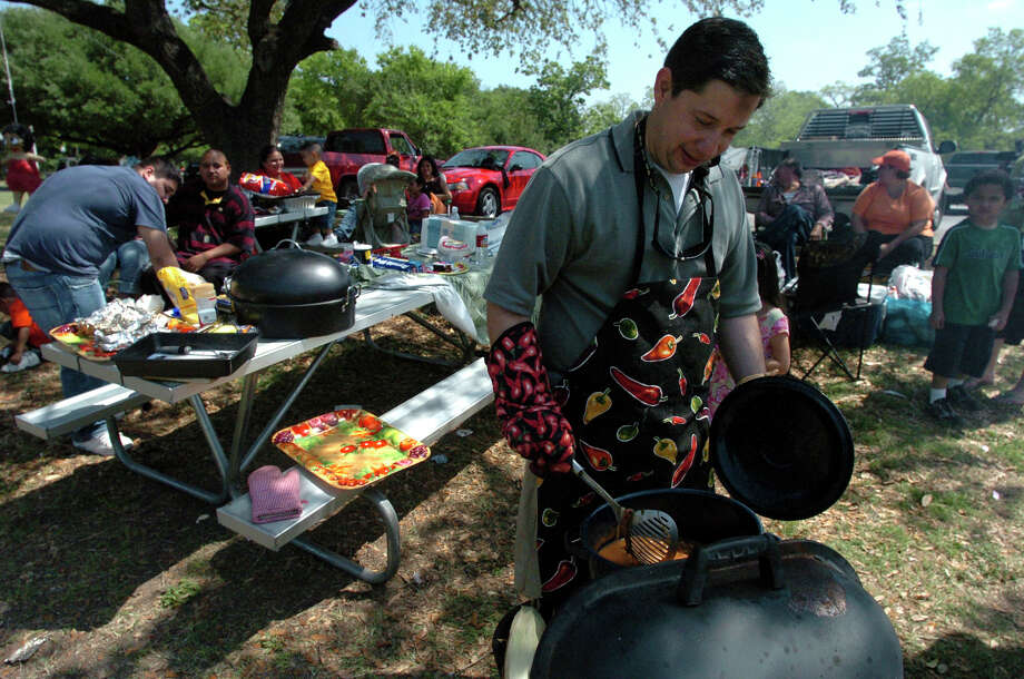 Arthur Perez stirs a pot of beans on a barbecue grill at Brackenridge Park on Sunday April 16, 2006. The Perez family had about 30 family members there for the celebration and have been going to the same spot at the park on Easter for more than 30 years. Photo: JOHN DAVENPORT, SAN ANTONIO EXPRESS-NEWS / SAN ANTONIO EXPRESS-NEWS