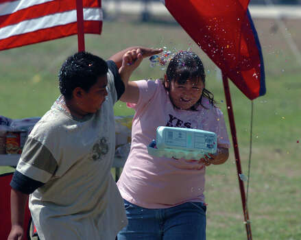 Steven Sanchez, 11, (L) gets into the spring spirit by cracking a cascarone over the head of his sister Ashley Sanchez, 9, while spending time on Easter Sunday 2006 at Brackenridge Park.  Photo: JOHN DAVENPORT, SAN ANTONIO EXPRESS-NEWS / SAN ANTONIO EXPRESS-NEWS