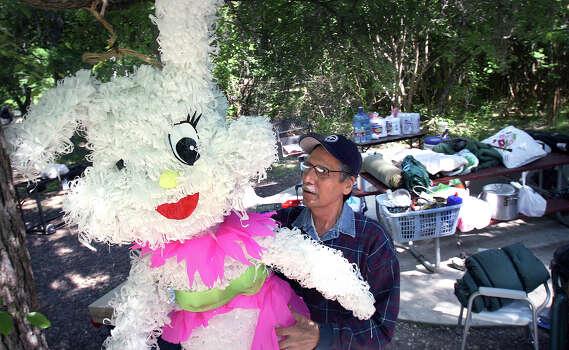 Oscar Mario Hernandez hangs his family's Easter bunny pinata at thier picnic site in Brackenridge Park, in preparation for Easter Sunday, Thursday April 5, 2007. Photo: Bob Owen, SAN ANTONIO EXPRESS-NEWS / SAN ANTONIO EXPRESS-NEWS