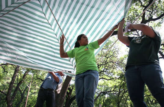 Roxann Rodriguez, center, holds a canopy up while her sister Trisha Rodriguez, right, and David Valenzuela, left, assemble the poles as their families prepare for Easter Sunday picnic in Brackenridge Park, Thursday April 5, 2007. Photo: Bob Owen, SAN ANTONIO EXPRESS-NEWS / SAN ANTONIO EXPRESS-NEWS