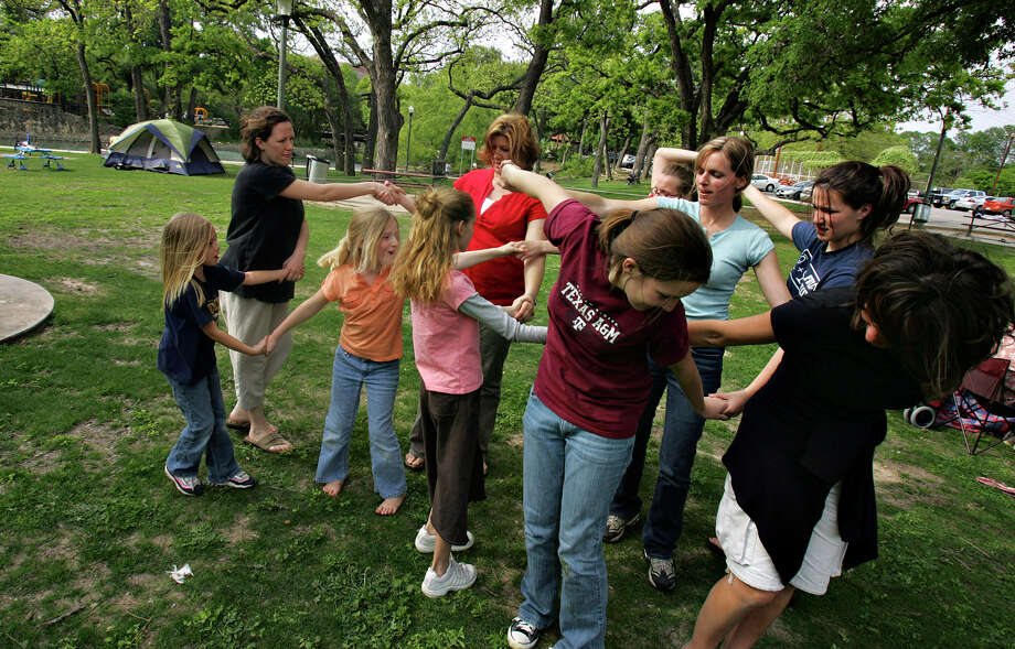 The Barton family tries to unwind a human knot during an outing Friday, April 6, 2007 at Brackenridge Park. The family spent the day at the park enjoying each other's company. Photo: BAHRAM MARK SOBHANI, SAN ANTONIO EXPRESS NEWS / SAN ANTONIO EXPRESS NEWS