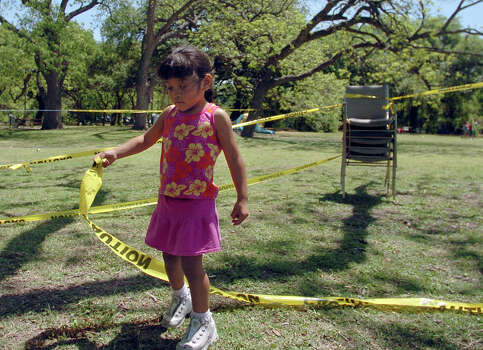Eunice Hernandez plays with the yellow boundary tape her family is using to stake their spot in Brackenridge Park in 2006 in preparation for the Easter Sunday picnic that many will enjoy at the park. Photo: BILLY CALZADA, SAN ANTONIO EXPRESS-NEWS / SAN ANTONIO EXPRESS-NEWS
