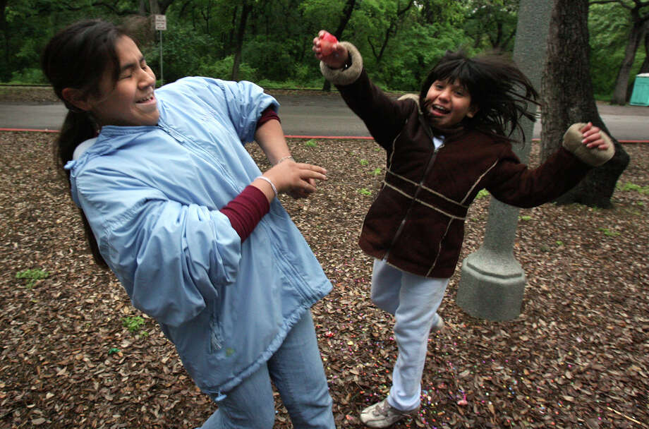 Roxann Rodriguez, 12, (L) tries to avoid a cascarone attack from Brittany Jimenez, 9, while their families were camping out at Brackenridge Park Easter Sunday 2007. The girls were there enjoying the weekend and were looking forward to Fiesta.  Photo: JOHN DAVENPORT, SAN ANTONIO EXPRESS-NEWS / SAN ANTONIO EXPRESS-NEWS