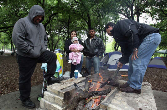 Walter Jimenez (L to rt.), Sara Hernandez, Ariana Limon, seven months, Art Limon, and David Valenzuela keep warm around the fire on Easter morning 2007 at Brackenridge Park. The group of friends and family have been carrying on the Easter camping tradition for years regardless of weather conditions.  Photo: JOHN DAVENPORT, SAN ANTONIO EXPRESS-NEWS / SAN ANTONIO EXPRESS-NEWS