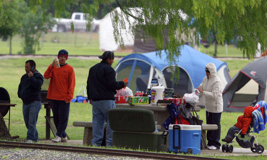 Daniel Semanko (L) talks on the phone while family members prepare for their Easter Sunday 2007 at Brackenridge Park near St. Mary's street. Semanko said he's been camping out there during Easter weekend for at least 21 years. With Semanko is Daniel Semanko, Jr., Joe Trevino (back turned), Sammy Garcia, and Troy X. Trevino, 2 years.  Photo: JOHN DAVENPORT, SAN ANTONIO EXPRESS-NEWS / SAN ANTONIO EXPRESS-NEWS