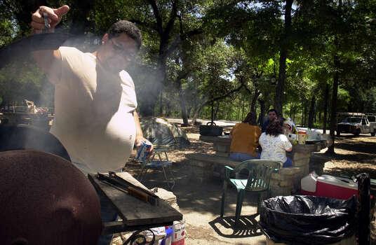 Pete Salinas checks his chicken cooking on a grill in Brackenridge Park in 2000. Photo: BOB OWEN, EN / EN