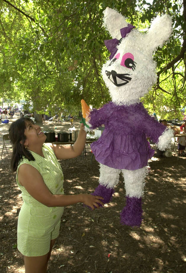 Edna Galeote helps raise a pinata Easter Sunday afternoon April 23, 2000 at Brackenridge Park. Galeote said she expected 60 friends and family members to join in their annual celebration. Photo: WILLIAM LUTHER, EN / EN