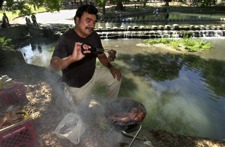 With a high vantage point overlooking the San Antonio River, Antonio Galindo, 53, of Brownsville, Texas, cooks the Easter Day meal at Brackenridge Park on Sunday, April 23, 2000. Galindo came to San Antonio to spend the weekend with his daughters. Photo: JERRY LARA, SAN ANTONIO EXPRESS-NEWS / EN