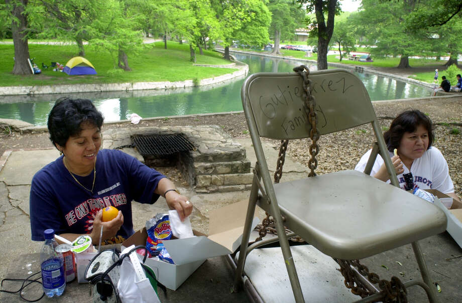 Maria Mendez, left, and Andrea Chavez, both from Houston, sit to eat lunch at a table reserved by the Gutierrez family Saturday, April 14, 2001 at Brackenridge Park. The two said they were surprised to see a chair chained to the table to reserve it.  Photo: BAHRAM MARK SOBHANI, EN / EN