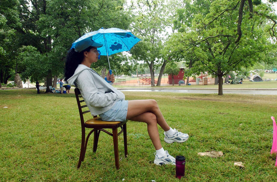 With umbrella in hand, Mayra Tellez waits it out at Brackenridge on Easter Sunday, April 20, 2003. Photo: JERRY LARA, SAN ANTONIO EXPRESS-NEWS / SAN ANTONIO EXPRESS-NEWS