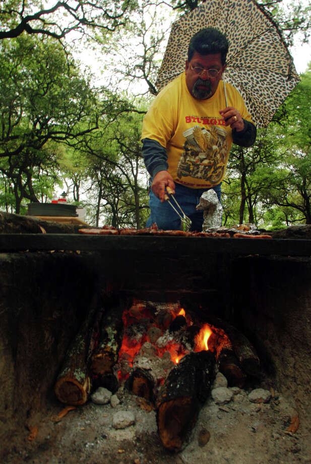 Floyd Nunez barbecues for his family Saturday, March 26, 2005 at Brackenridge Park. He said they try to come to the park annually for Easter, but this is only the second time they have been able to get a good spot for camping.  Photo: BAHRAM MARK SOBHANI, SAN ANTONIO EXPRESS NEWS / SAN ANTONIO EXPRESS NEWS