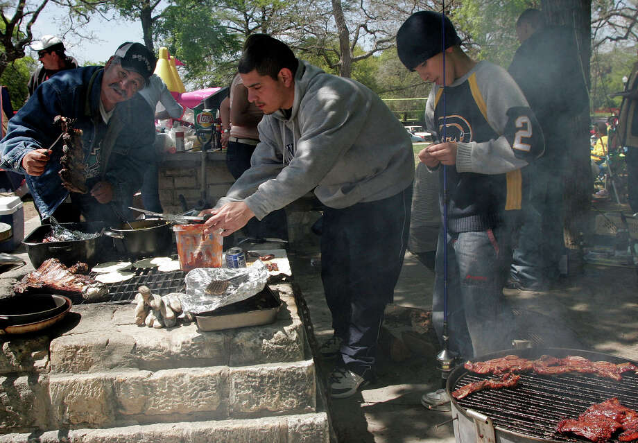 Easter morning found Brackenridge Park full of campers, families preparing for Sunday picnics and folks working on staying warm in the face of a chilling wind. Here, by noon, things had warmed up to where most people were fully engaged in springtime outdoor activities. From the left, Joe Flores and Michael Medellin tend to the bar-b-que while Isidro Vela, 13, prepares to try his luck fishing. 03/27/05  Photo: J. MICHAEL SHORT, SPECIAL TO THE EXPRESS-NEWS / SAN ANTONIO EXPRESS-NEWS