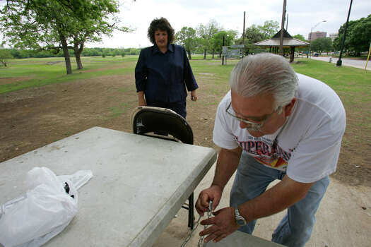 Letty Morales-Bissaro, 41, watches as her dad, Paul Morales, 61, locks up a space at Brackenridge Park on Tuesday, April 11, 2006.  Photo: JERRY LARA, SAN ANTONIO EXPRESS-NEWS / SAN ANTONIO EXPRESS-NEWS