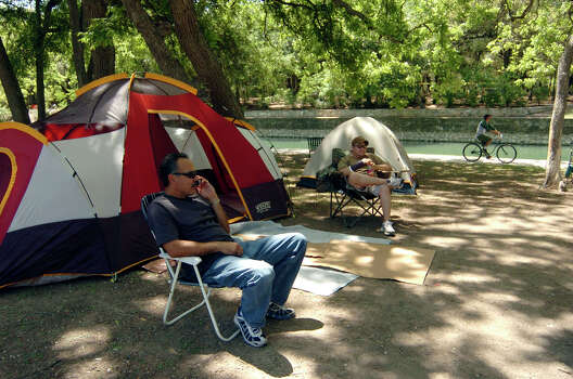 Mike Salinas chats on his cell phone in 2006 as his son-in-law, Hector Varela, sits by at the campsite that they have staked out at Brackenridge Park in preparation for the family Easter Sunday outing.  Photo: BILLY CALZADA, SAN ANTONIO EXPRESS-NEWS / SAN ANTONIO EXPRESS-NEWS