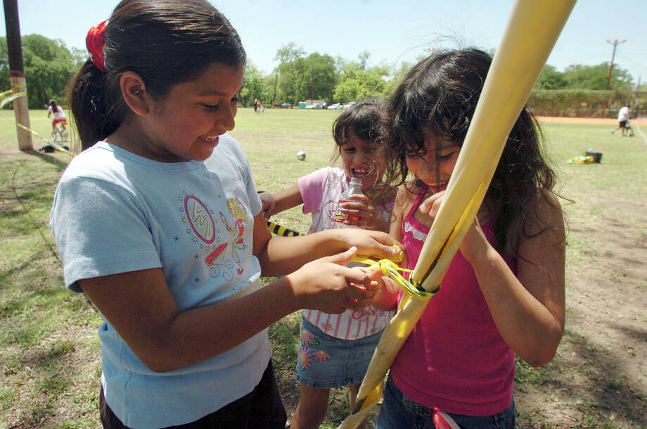 Destiny Castro, left, Eunice Hernandez and Araceli Hernandez tie boundary tape on Friday, April 14, 2006, around their campsite to reserve for their outing at Brackenridge Park on Easter Sunday.  Photo: BILLY CALZADA, SAN ANTONIO EXPRESS-NEWS / SAN ANTONIO EXPRESS-NEWS