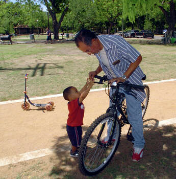 Heriberto Hernandez enjoys a moment with his 20-month-old grandson, Kaleb Hernandez, at Brackenridge Park in 2006, where the Hernandez family was busy on Friday staking out their spot for Sunday's Easter celebration.  Photo: BILLY CALZADA, SAN ANTONIO EXPRESS-NEWS / SAN ANTONIO EXPRESS-NEWS
