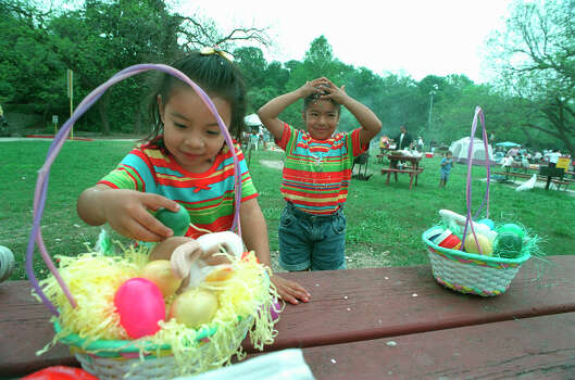 Four year old Carolina Ortiz reaches into a her Easter basket Sunday April 4, 1999, as her sister, Marisol Ortiz 6, wipes the confetti off her head at Brackenridge Park. Photo: GLORIA FERNIZ, SAN ANTONIO EXPRESS-NEWS / SAN ANTONIO EXPRESS-NEWS