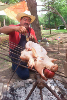 Ernest Cerna tends to a pig his family was roasting Saturday afternoon April 3, 1999 at Brackenridge Park geting ready for Easter Sunday. Cerna's family, which will be approximately 100 strong Sunday in the park, hs been celebrating the Easter weekend and claiming theri favorite sport for 40 years. The family, working in shifts, has been staking out their sport since Tuesday. Photo: Rick Hunter