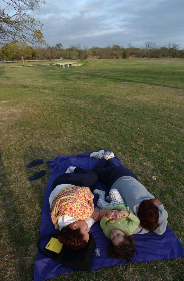 From left, Maria Trevi o, 21, her daughter, Briana Rodrguez, 2, and her mother, Leticia Trevi o hang out at Brackenridge Park on Wednesday, March 27, 2002. They said that the Park Rangers won't allow them to campout so they have arrived around 7:00 a.m. each morning since Monday and leaving at 11:00 p.m. in order to reserve a spot for the Sunday Holiday. Photo: JERRY LARA, SAN ANTONIO EXPRESS-NEWS