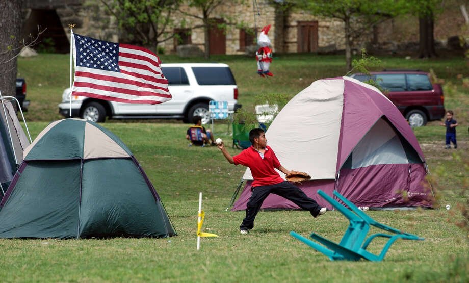 Matthew Castro plays catch with his dad (Gilbert, not pictured) amidst their tents Saturday, March 30, 2002 at Brackenridge Park. Photo: BAHRAM MARK SOBHANI, SAN ANTONIO EXPRESS-NEWS / SAN ANTONIO EXPRESS-NEWS